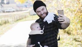 Тысячелетний папа с младенцем в идя несущей внешнем & принимая Sel стоковые фотографии rf