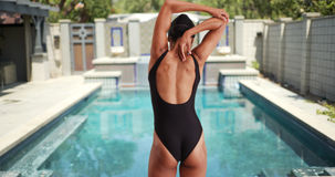 Тысячелетний пловец женщины смешанной гонки протягивая перед скакать в бассейн Стоковое Изображение RF