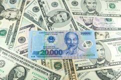 20 тысяч въетнамский VND сделанный на предпосылке много долларов Стоковая Фотография RF