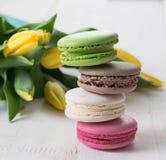 Тюльпаны и чашка чаю некоторых macaroons желтые на деревянном утре дня матерей весны таблицы стоковая фотография