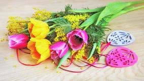 Тюльпаны, мимоза и украшения пасхи на деревянной предпосылке Стоковые Фотографии RF
