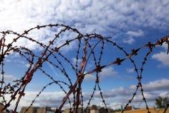 тюрьма абстрактный колючий провод иллюстрации схематической конструкции Колючая проволока на предпосылке голубого неба с белыми о Стоковое Изображение