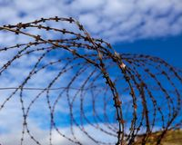 тюрьма абстрактный колючий провод иллюстрации схематической конструкции Колючая проволока на предпосылке голубого неба с белыми о Стоковые Изображения