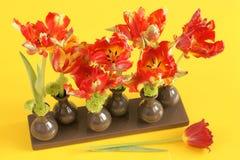 Тюльпаны в вазах на желтом цвете Стоковое фото RF