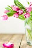 Тюльпаны в вазе и свече горения Стоковые Изображения