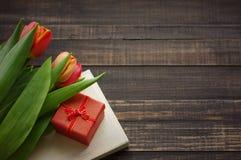 Тюльпаны, книга и коробка подарка красная на деревянной поверхности Стоковая Фотография