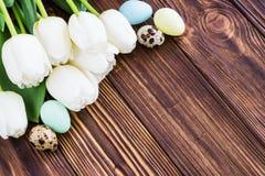 Тюльпан букета белый цветет с пасхальными яйцами на старом деревянном tabl Стоковое фото RF
