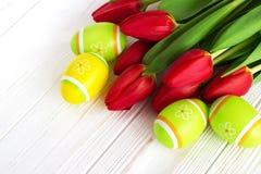 Тюльпан букета красный цветет с пасхальными яйцами на старом деревянном столе Стоковые Фото