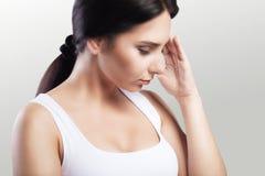 Тягостное состояние Девушка головных болей молодая красивая держит ее руку на ее голове мигрень холодно Принципиальная схема здор стоковое фото