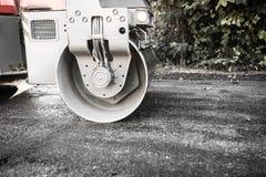 Тяжелая машина свертывает новую дорогу асфальта Стоковые Фото