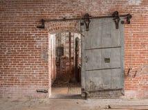 Тяжелая сползая дверь металла промышленная в старом складе Стоковые Фотографии RF