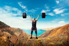 Тяжелоатлет принимает вес на верхней части горы стоковые фото