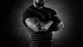 Тяжелоатлет стоит в угрожающем представлении с пересеченной огромной рукой Стоковое фото RF