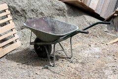 Тяжело - используемая тележка конструкции тачки при 2 ручки и одиночного колесо выведенные на строительную площадку стоковое фото rf