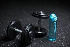 Тяжелые стальные гантели, голубая бутылка для воды, оборудования для спорт по заведенному порядку на темноте запачкали предпосылк Стоковые Фото
