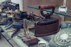Тяжелый металлический утюг антиквариата и другие вещи на счетчике античного магазина стоковые фото