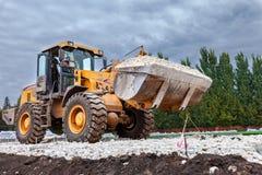 Тяжелая загрузка бульдозера и moving гравий на месте строительства дорог стоковое фото