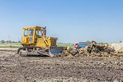 Тяжелая машина конструкции earthmover двигает землю на buildin стоковые изображения rf