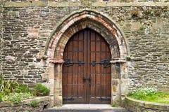 Тяжелые богато украшенные деревянные двери в старом каменном здании Стоковая Фотография RF