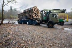 Тяжелый грузовик для транспорта журналов стоя на банке r Стоковая Фотография