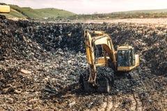 Тяжелый затяжелитель экскаватора, бульдозер работая в свалке мусора Рециркулировать и вопросы защиты окружающей среды Стоковые Фото