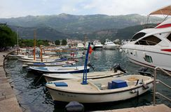 Тhe colorful port of Budva, Montenegro. Single boats standing in the port. Sea yacht to port. Big mountain in the distance stock photo