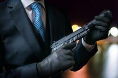 Убийца держит оружие с звукоглушителем в руках на ноче стоковые фотографии rf