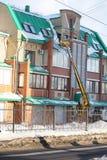 Уборка очищает снег от крыши дома Стоковые Фото