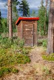 Уборная во дворе в лесе в Норвегии стоковые фото