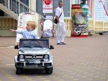 Уборная Сочи, Россия, 08 31 2017: Маленький белокурый мальчик едет электрический автомобиль в первый раз стоковое изображение rf
