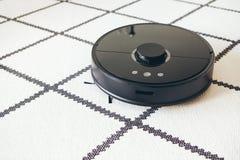 Уборщик робота вакуума с умной навигацией делает отечественное домашнее хозяйство - очищая белый ковер Управление удаленных и тел стоковое изображение