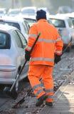 Уборщик улицы с оранжевой курткой которая очищает улицы Стоковые Изображения RF