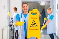 Уборщица показывая предупредительный знак стоковая фотография