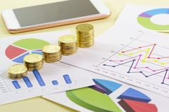 Увеличение в размере стога золотых монет на покрашенных диаграммах Визуальный анализ государства дела стоковое изображение rf