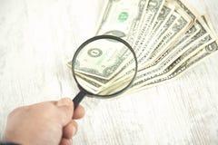 Увеличитель руки человека на деньгах стоковое изображение