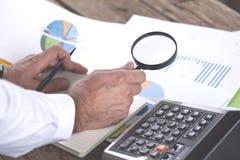 Увеличитель руки человека с калькулятором и диаграммой стоковая фотография