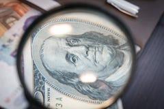 Увеличитель сфокусировал на банкноте 100 долларов, евро, долларе, банкнотах reminbi Стоковые Изображения