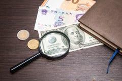 Увеличитель сфокусировал на банкноте 100 долларов, евро, долларе, банкнотах reminbi Стоковая Фотография
