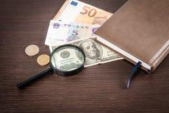 Увеличитель сфокусировал на банкноте 100 долларов, евро, долларе, банкнотах reminbi Стоковые Фотографии RF
