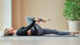 Уверенная атлетическая молодая женщина лежа на циновке делая протягивать после тренировать дома акции видеоматериалы
