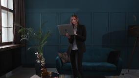 Уверенная деятельность коммерсантки на ноутбуке в ее современном голубом современном интерьере офиса Стильный красивый делать жен видеоматериал