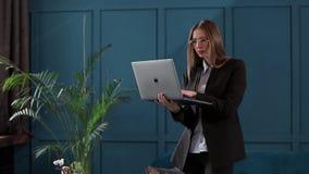 Уверенная деятельность коммерсантки на ноутбуке в ее современном голубом современном интерьере офиса Стильный красивый делать жен акции видеоматериалы