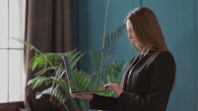 Уверенная деятельность коммерсантки на ноутбуке в ее современном голубом современном интерьере офиса Стильный красивый делать жен сток-видео