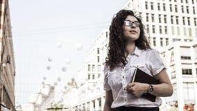 Уверенная и милая молодая женщина с черным вьющиеся волосы стоя на предпосылке зданий стоковые фото