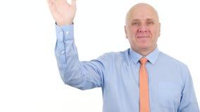 Уверенная улыбка бизнесмена смотря к камере и сделать здравствуйте жесты рукой акции видеоматериалы
