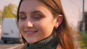 Уверенная усмехаясь кавказская женщина смотрит камеру точно, двигая и усмехаясь холодок пока стоящ на открытом воздухе близко сток-видео