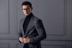 Уверенное, красивое bussinesman носит стильный серый костюм и черные eyeglasses и взгляды с ориентацией на камере стоковые фото