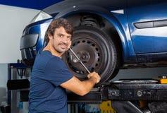 Уверенно автошина автомобиля отладки механика с ключем оправы Стоковые Фото