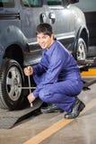 Уверенно автошина автомобиля отладки механика с ключем оправы Стоковая Фотография