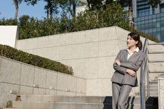 Уверенно азиатская бизнес-леди стоя в вне офисе внутри стоковое изображение